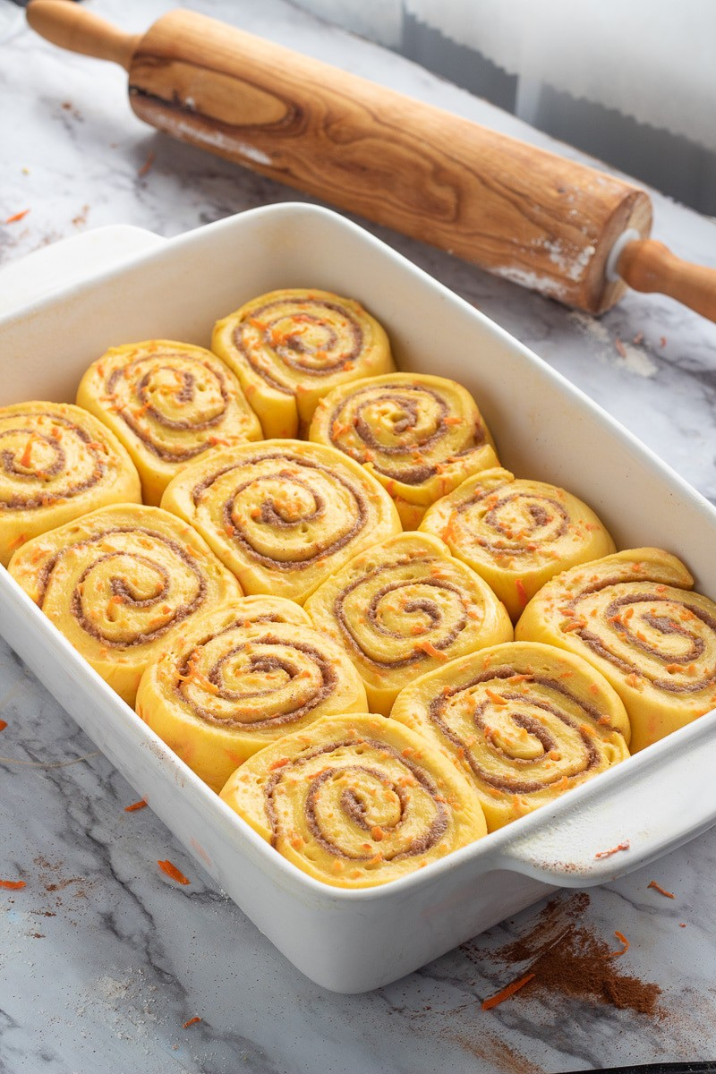 Raw carrot cake cinnamon rolls in white rectangle pan with rolling pin.