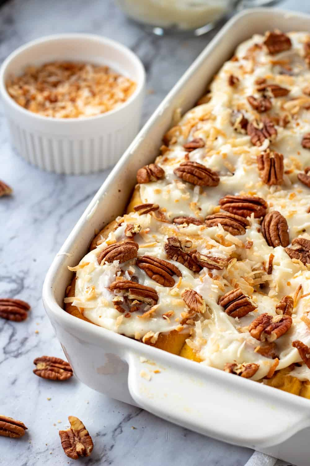Baked carrot cake cinnamon rolls in white pan with pecans and coconut on marble.