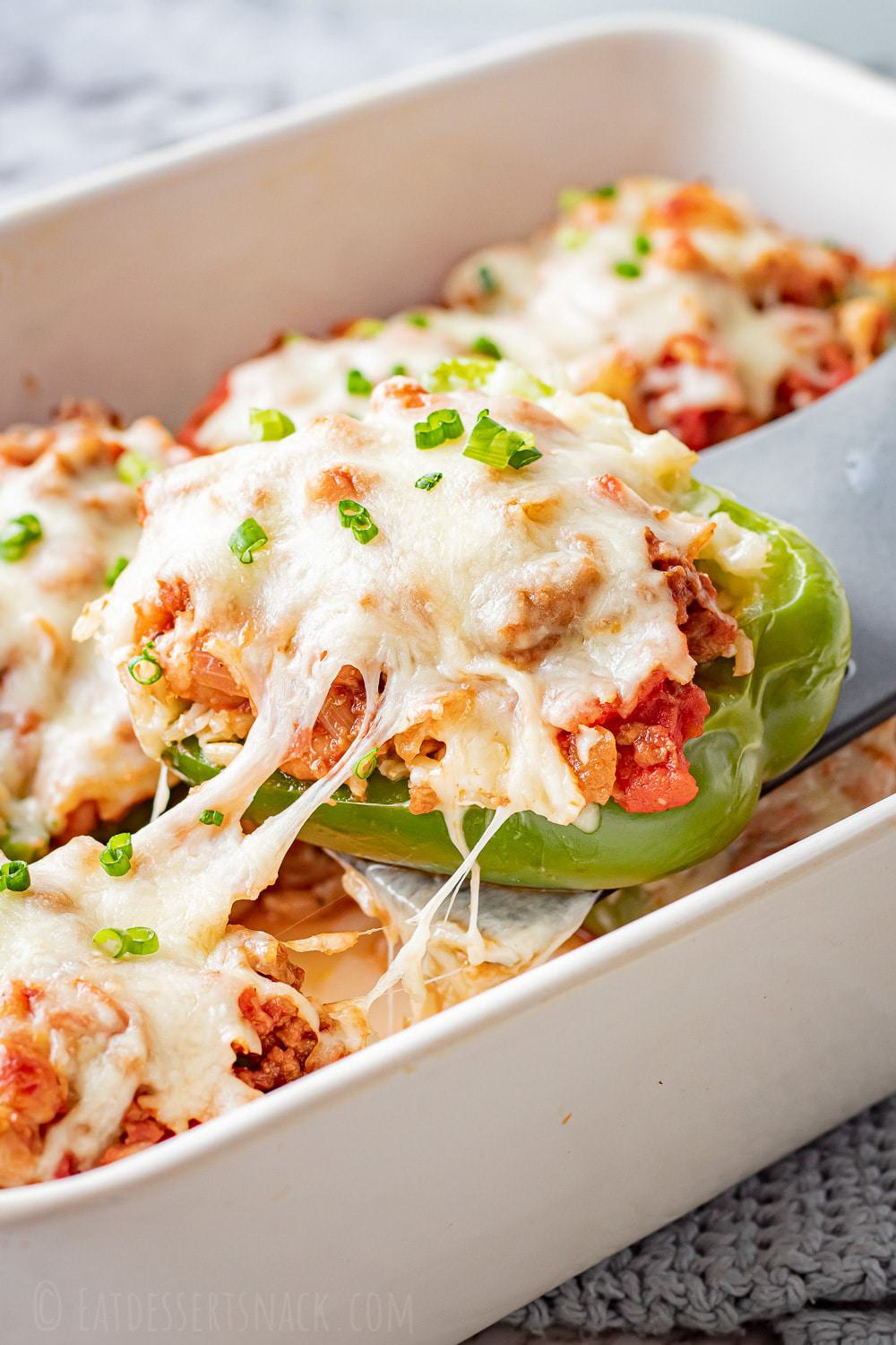 green bell pepper with ground beef filling, melted cheese on top in a white pan.