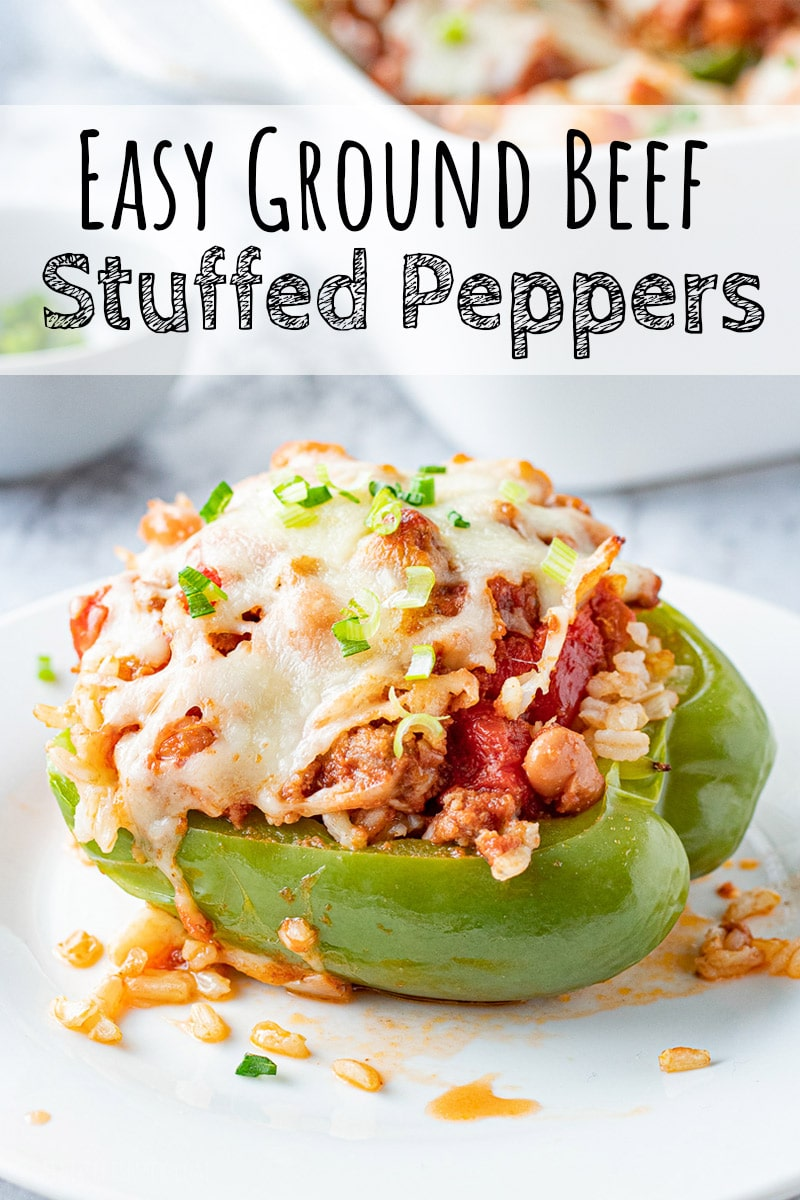 Cooked ground beef stuffed peppers with cheese on top with fork on a white plate.