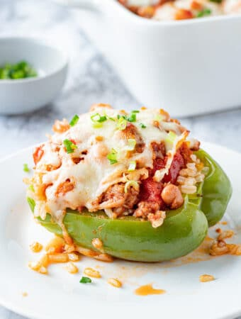 Cooked green pepper filled with ground beef, pinto beans, tomatoes, and cheese on top on a white plate.