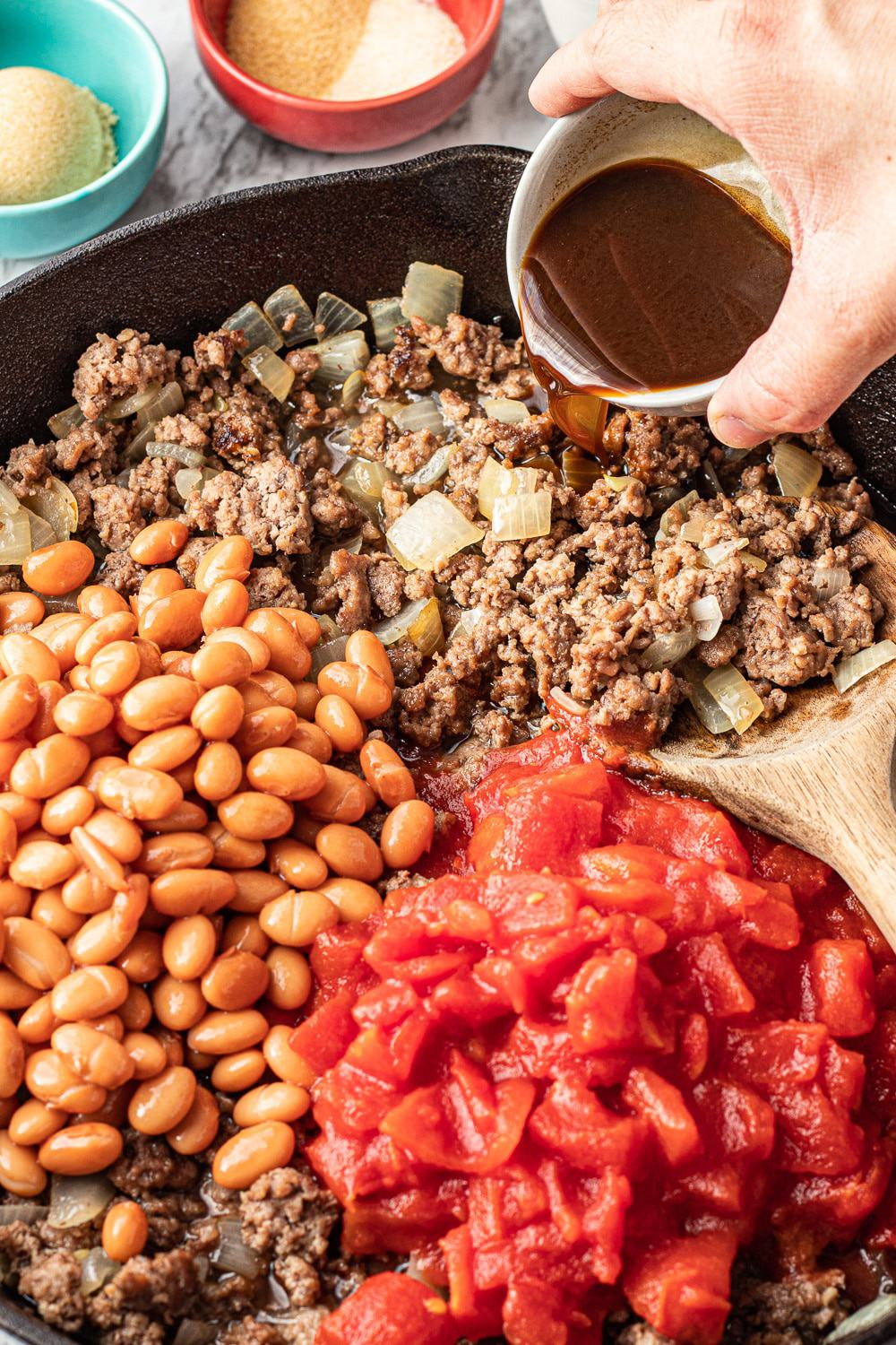 ground beef, tomatoes, and pinto beans cooked in a black frying pan.