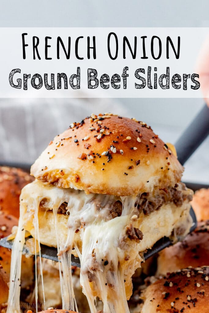 Dinner roll sliced in half with ground beef and caramelized onion filling with cheese on a black spatula with text overlay.