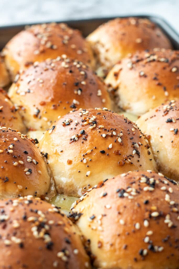 Dinner roll sliced in half with ground beef and caramelized onion filling with cheese in a dark pan with poppy seeds and sesame seeds on top.