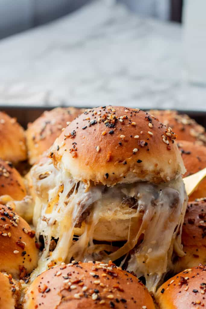 Dinner roll sliced in half with ground beef and caramelized onion filling with cheese on a gold fork.