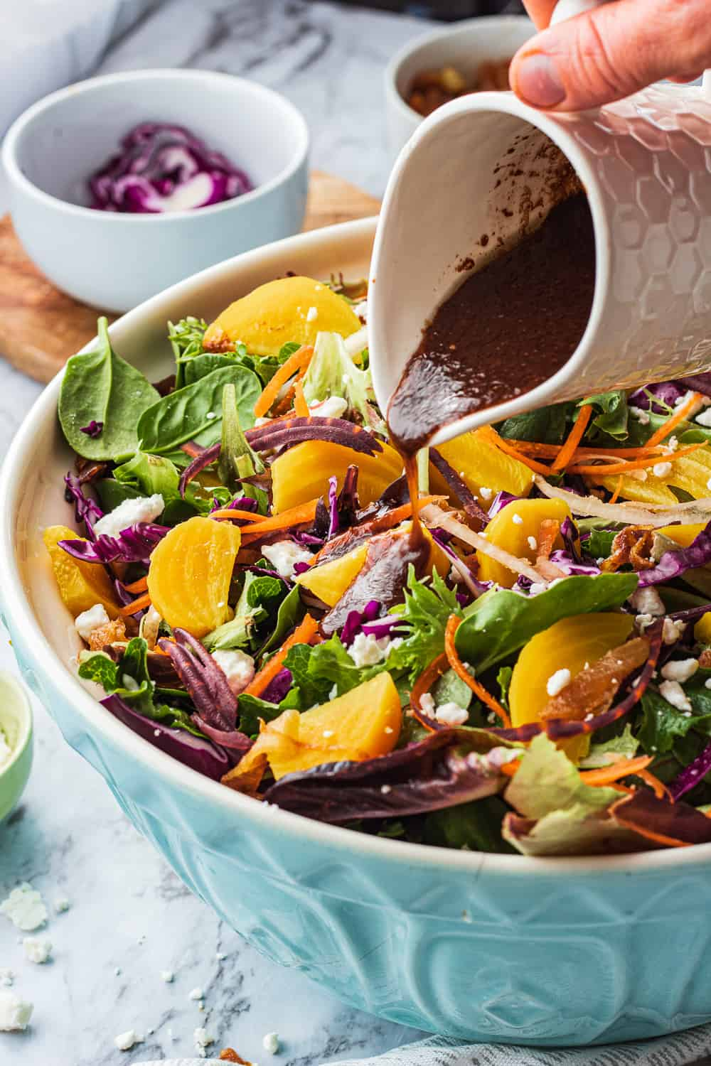 gold beets, red cabbage and carrots in a blue bowl with balsamic miso dressing pouring over salad.