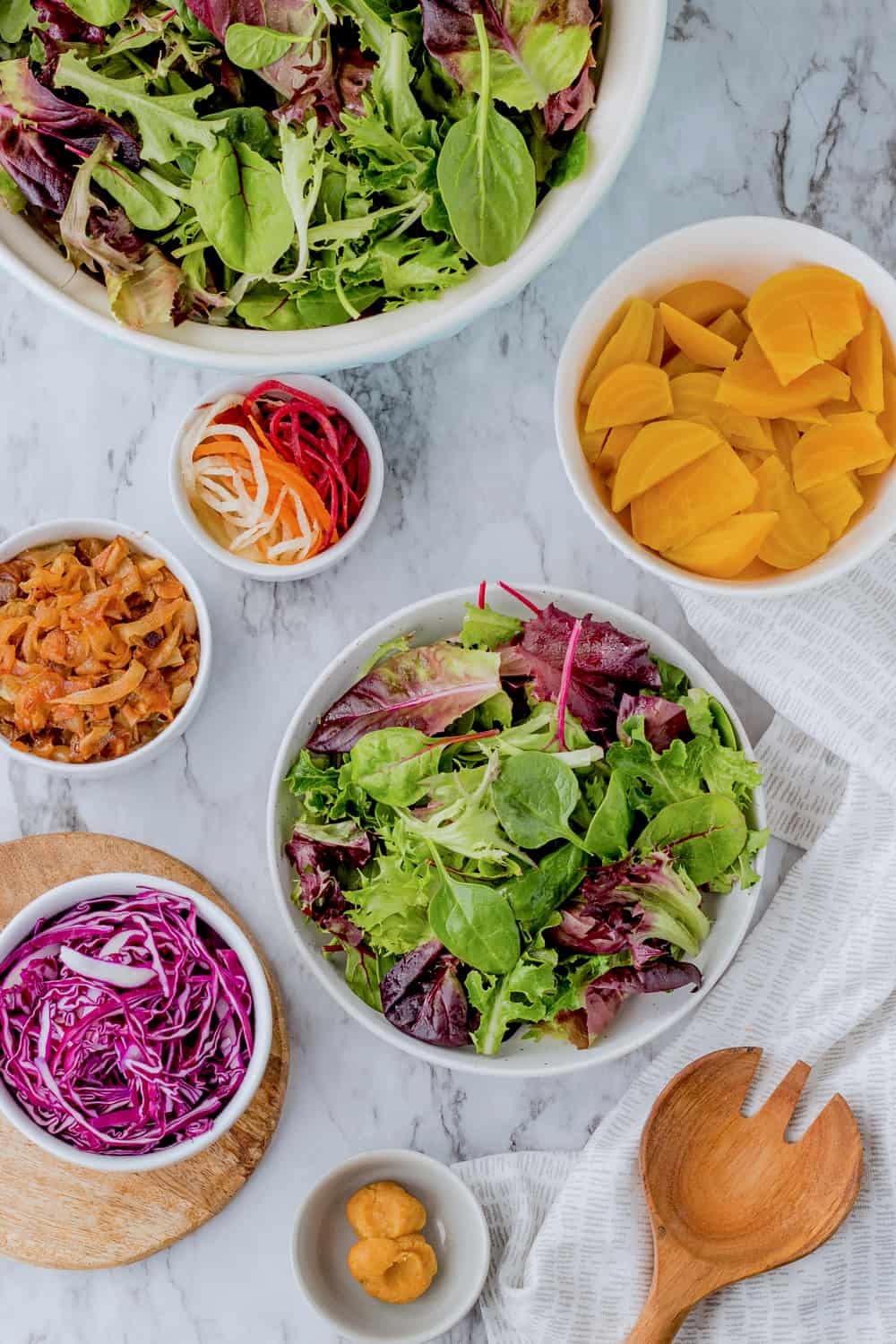 Lettuce, gold beets, caramelized onions, red cabbage, and miso in white bowls with wood spoon on marble.