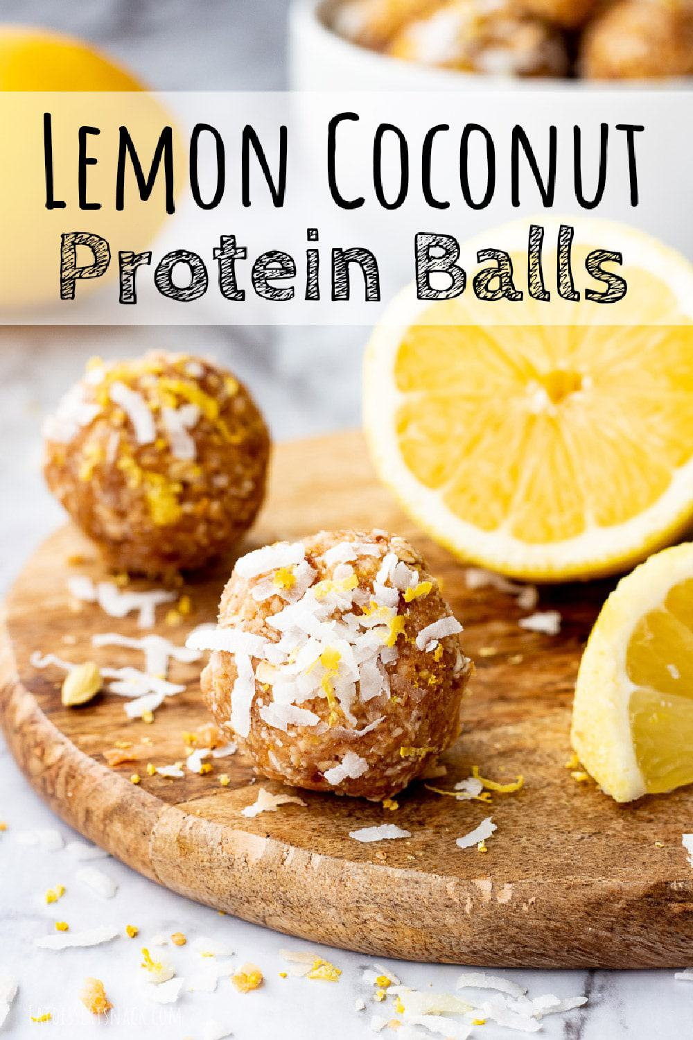 Lemon coconut protein ball on round wood board with sliced lemon with text overlay.