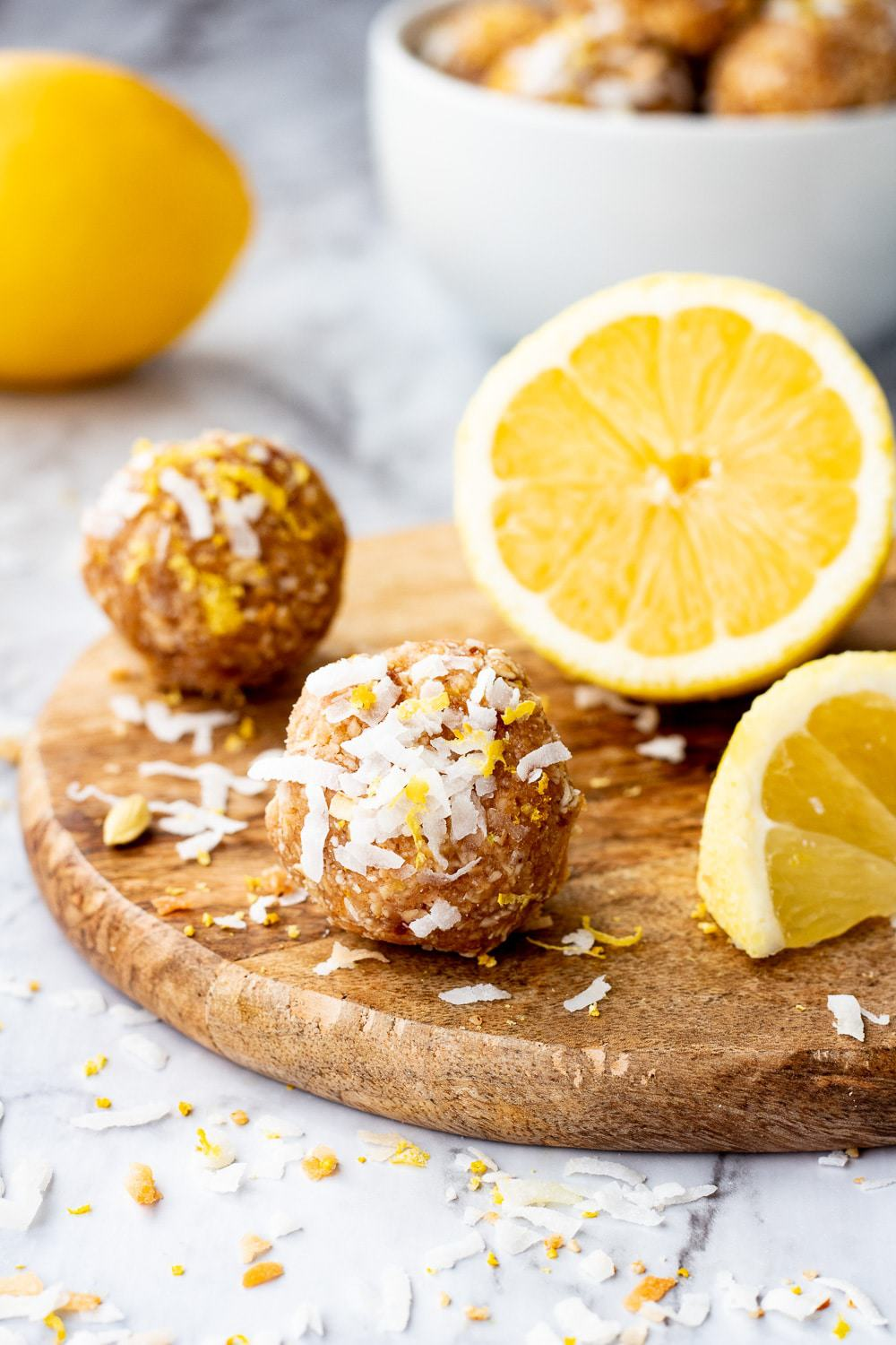 Lemon coconut protein ball on wood board with sliced lemon on marble backdrop.