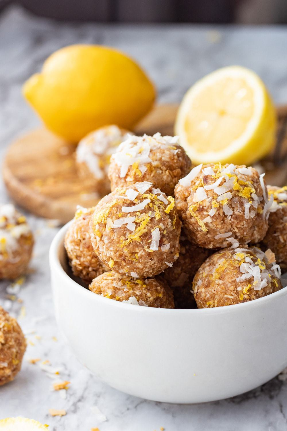Lemon Coconut protein balls in white bowl with whole lemon and slices in background on wood board.