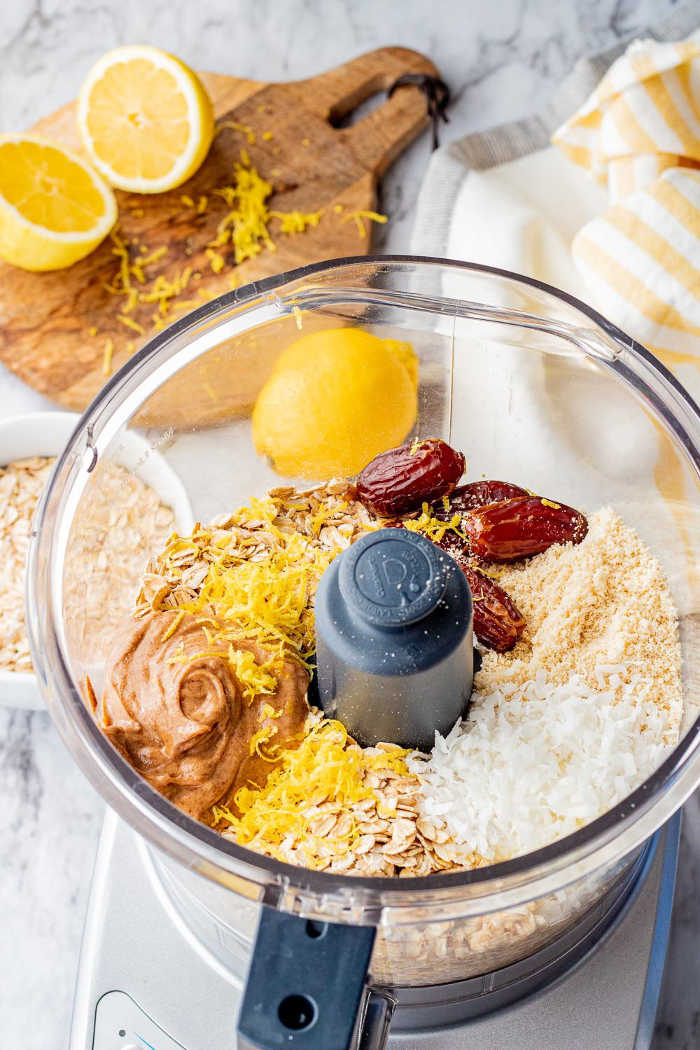 clear plastic bowl with dates, almond butter, almond flour, coconut flakes, oats, lemon zest and juice, and vanilla extract.