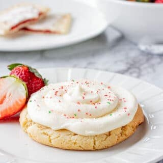 Baked strawberry poptart sugar cookie on a white plate with strawberries.