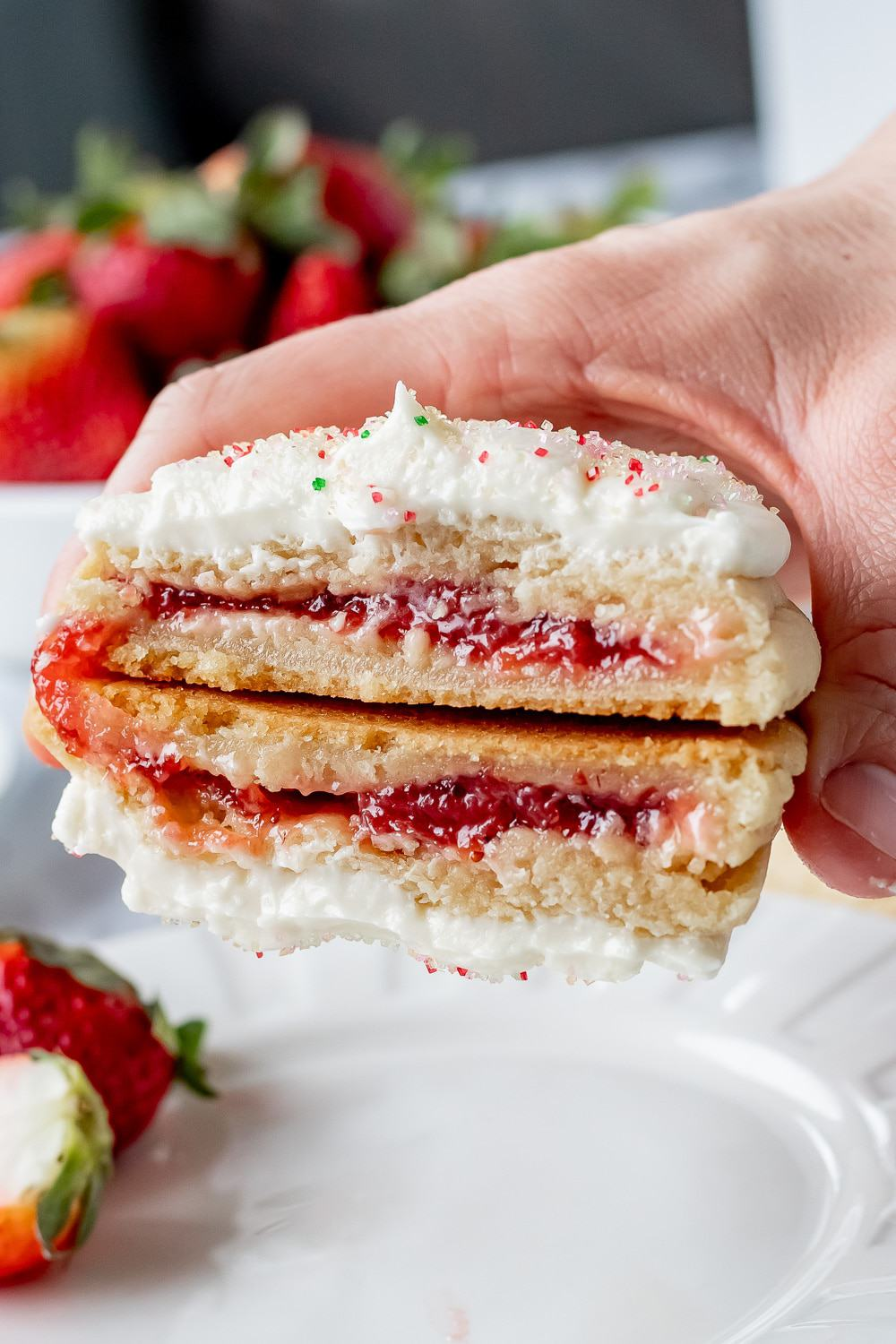 2 halves of strawberry pop tart cookie in a hand above a white plate with strawberries.