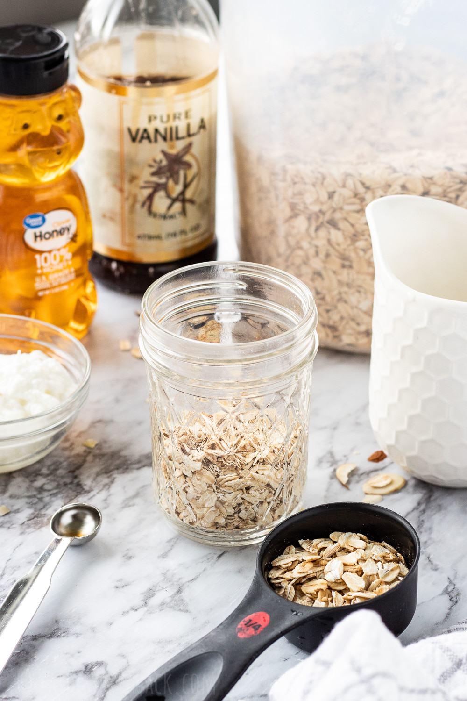 Jar of oats with honey, milk, yogurt and vanilla in background