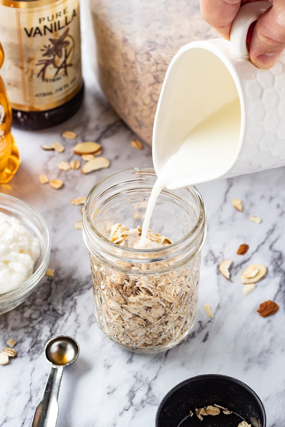 white measuring cup pouring milk into mason jar of oats on marble countertop.