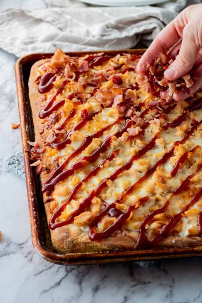 Hand sprinkling crumbled bacon onto baked bbq chicken sheet pan pizza.