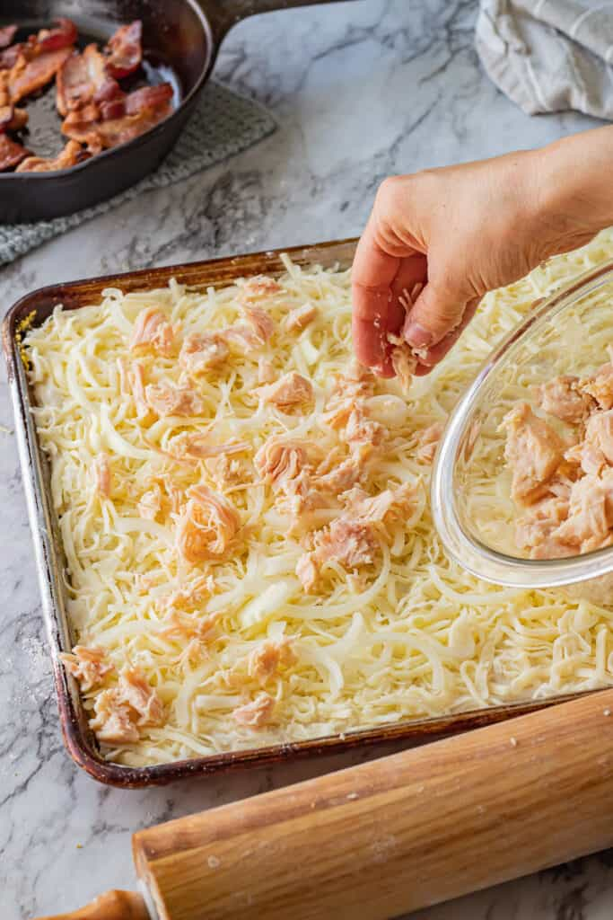 hand spreading chicken on sheet pan pizza.