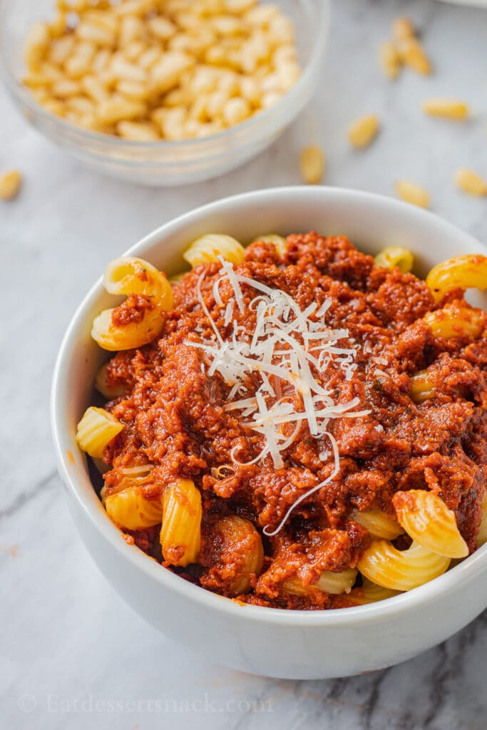 Red pesto on cavatappi pasta in white bowl with parmesan on marble.