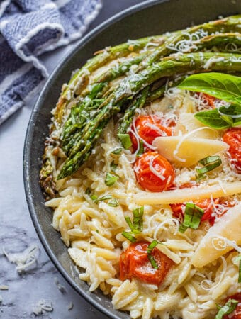 Black pan of cooked orzo, roasted asparagus and tomatoes, parmesan cheese on top with blue tea towel.