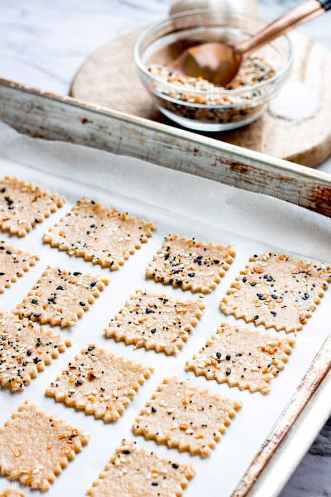 Raw sourdough crackers on baking sheet with bowl of spices in background.