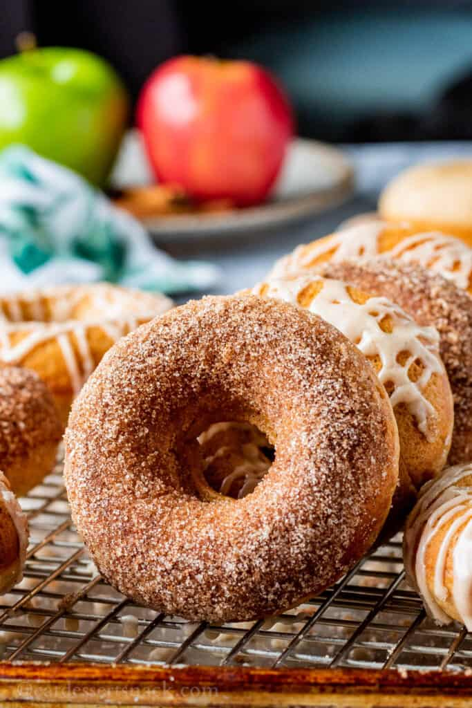 Baked apple cider donut on wire rack and metal pan with other baked donuts.